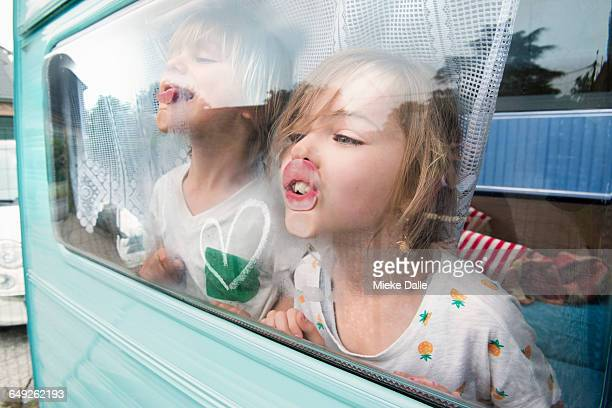 children pressing nose and lips against window