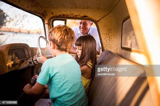 Children pretending to drive their grandfather's old vehicle