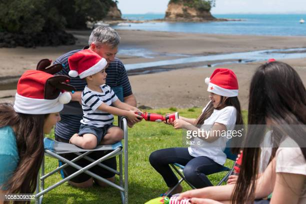 children pulling a christmas cracker at a beach party - southern hemisphere stock photos and pictures