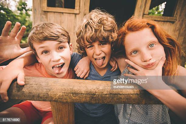 Children pulling silly faces at camera while in a treehouse