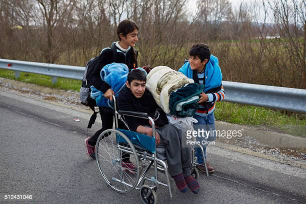 Children push a boy in a wheelchair along a road towards a refugee camp near the GreeceMacdonia border which has become overcrowded as refugees...