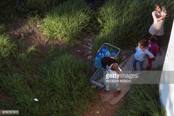 Children push a trolley full of bottles of water at the formerly deserted Helen Bowden Nurses home where people live illegally but without...