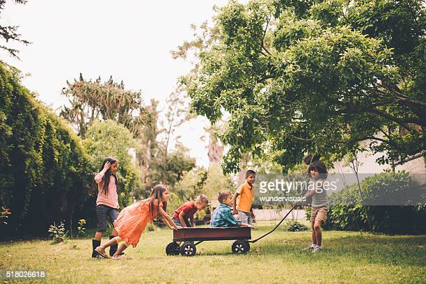 Children pushing and pulling friends in red wagon in park
