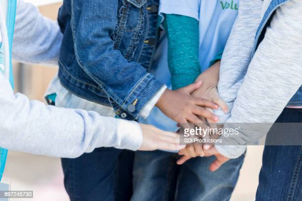 Children put their hands together in unity