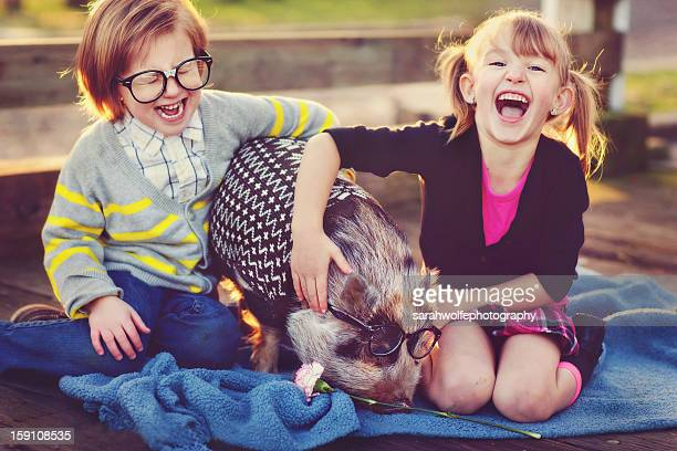 Children putting glasses on pig and laughing