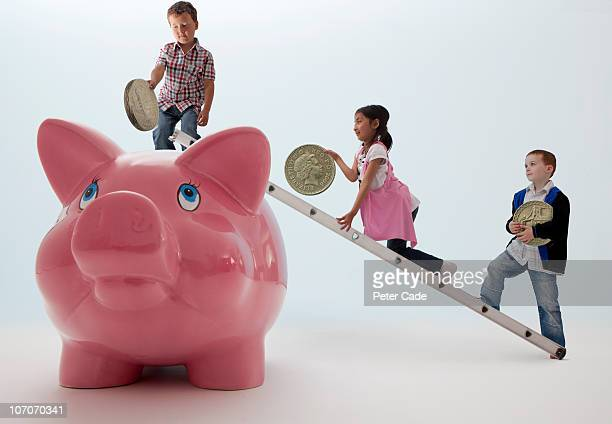 children putting pounds into giant piggy bank