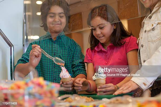 Children putting toppings on yogurt