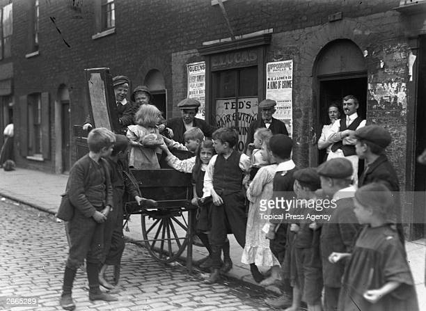 Children queue to get bread from a baker's cart during strikes in a poor district of the East End of London