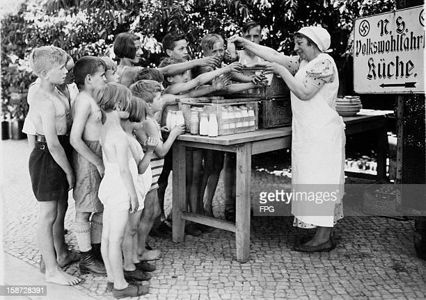 Children queue up for milk and cocoa distributed by the Nationalsozialistische Volkswohlfahrt or NSV at Wannsee Berlin Germany 1st July 1935