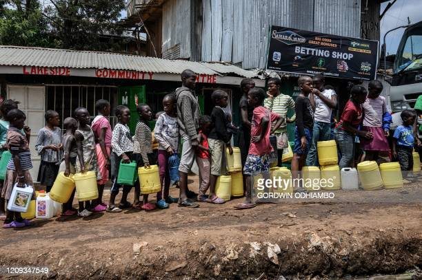 TOPSHOT Children queue with their jerrycans to fill them with free water distributed by the Kenyan government at Kibera slum in Nairobi Kenya on...
