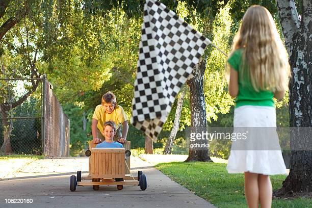 Kinder-Rennen in Push Go-Cart an einem sonnigen Tag
