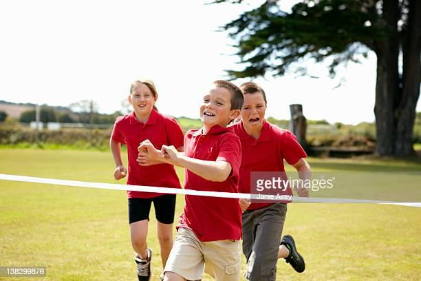 niños carreras hacia cross finish line - cruzar fotografías e imágenes de stock