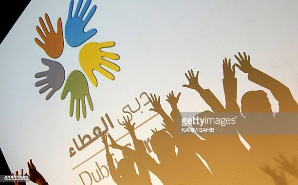 Children raise their hands during a ceremony for launching Dubai Cares' Volunteer Campaign in the Gulf emirate on November 2 2008 The campagin...