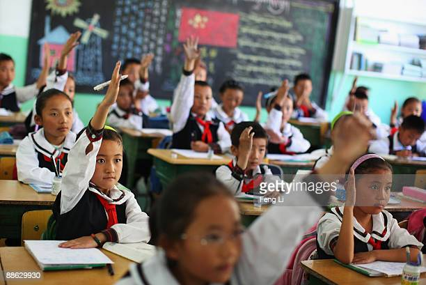 Children raise their hands to answer a question during a Tibetan language class at the Lhasa Experimental Primary School on June 19, 2009 in Lhasa,...
