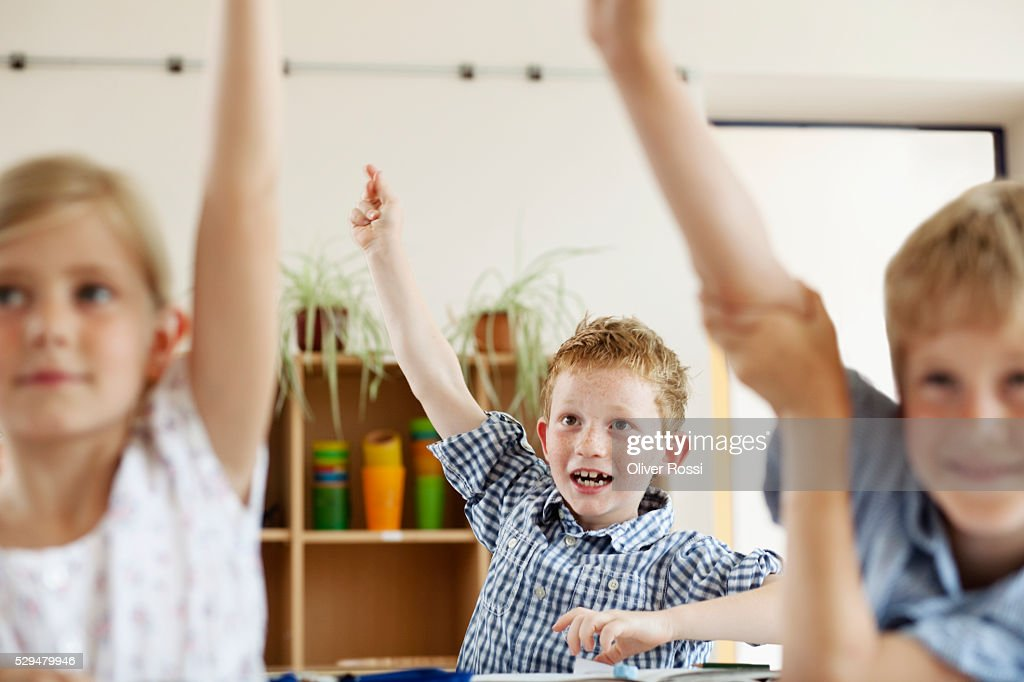 Children raising hands in classroom : Stock Photo