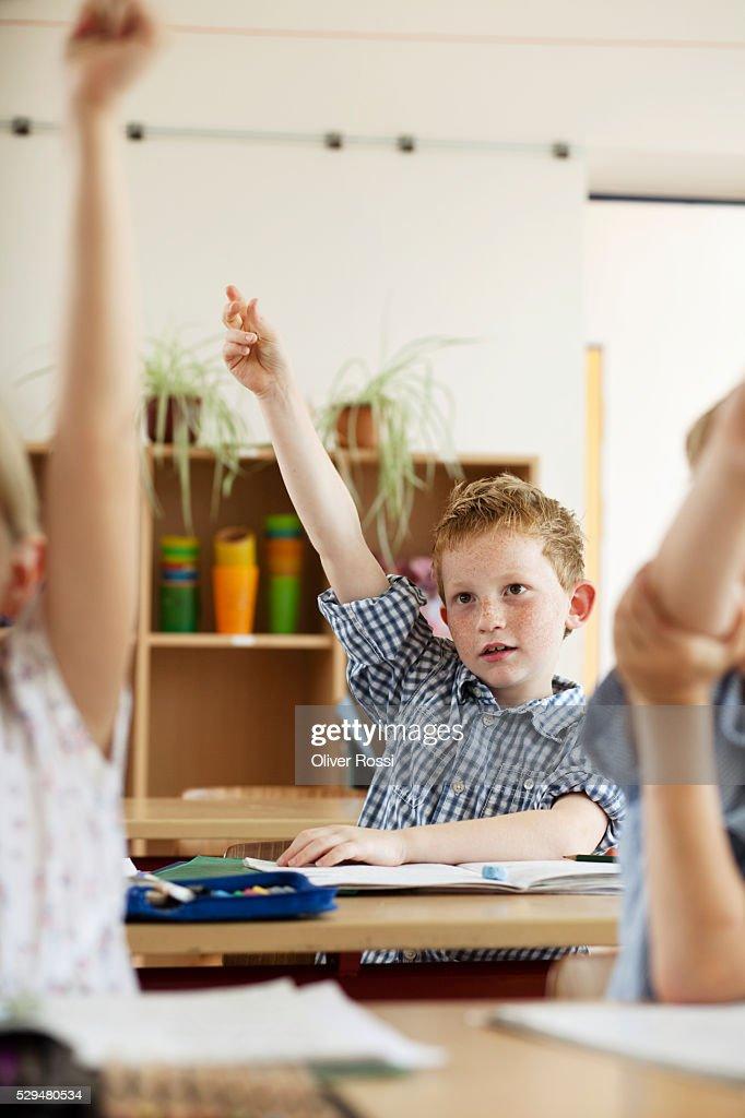 Children raising hands in classroom : Stockfoto