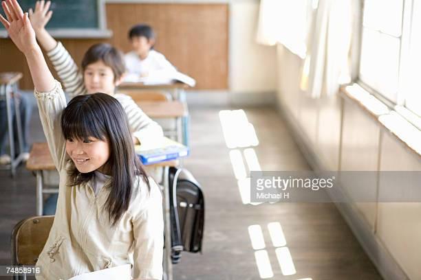 Children (6-9) raising hands in school classroom