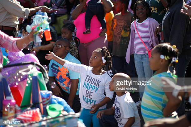 Children reach for bubbles at the 29th annual Kingdom Day Parade on January 20 2014 in Los Angeles California The Kingdom Day Parade honors the...