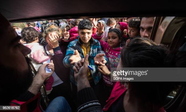 Children reach out to Kurdish Red Crescent aid workers distributing milk outside of Tall Rifat An estimated 400000 refugees fleeing the twomonthold...