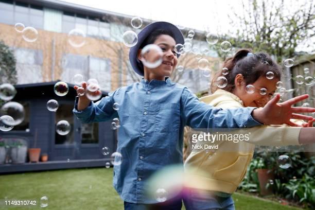 children reaching to catch bubbles in back garden - nur kinder stock-fotos und bilder