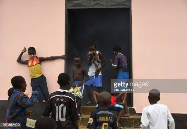 Children react as agents of the National Institute of Public Hygene carry out fumigation in the Anyama district of Abidjan on June 9 as part of the...