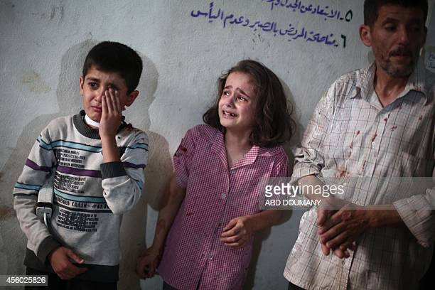 Children react as they stand at a makeshift hospital in the besieged rebel bastion of Douma northeast of the Syrian capital Damascus on September 24...