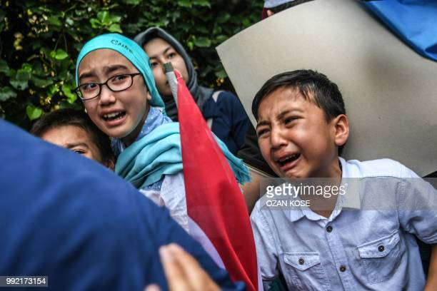 Children react as Turkish plain clothes police officers try to push back demonstrators during a protest of supporters of the mostly Muslim Uighur...