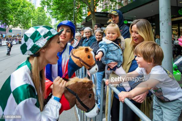 Children react to toy horses held by performers during the 2019 Melbourne Cup Parade on November 04 2019 in Melbourne Australia