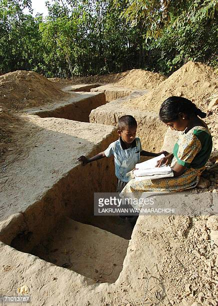 Children read a book while sitting in a selfdefence bunker in the Tamil rebelcontrolled village of Uthayanagar East near Kilinochchi 23 May 2006...