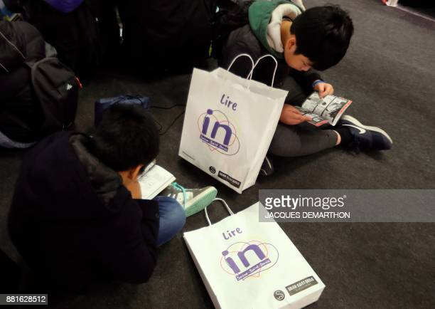 Children read at the Salon du livre et de la presse jeunesse in Montreuil eastern Paris on November 29 2017 DEMARTHON