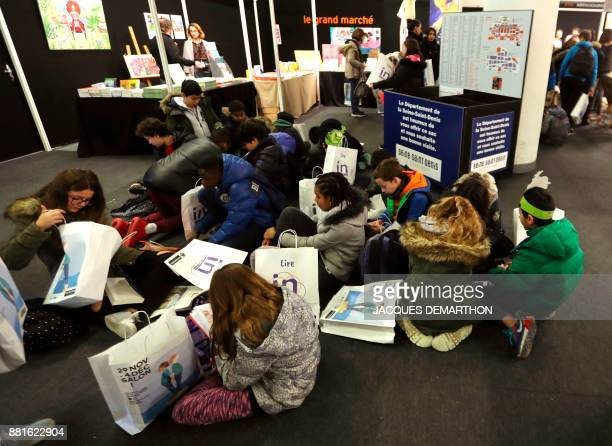 Children read near a SeineSaintDenis department's stand at the Salon du livre et de la presse jeunesse in Montreuil eastern Paris on November 29 2017...