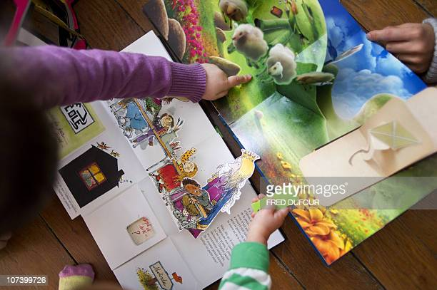 Children read pop-up books, three-dimensional or movable books, on December 04, 2010 in Paris. Pop-up books made known in the 19th century by German...