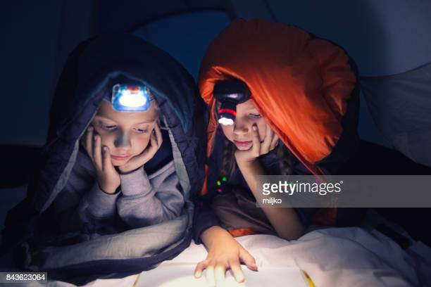Children reading a book on camping at night