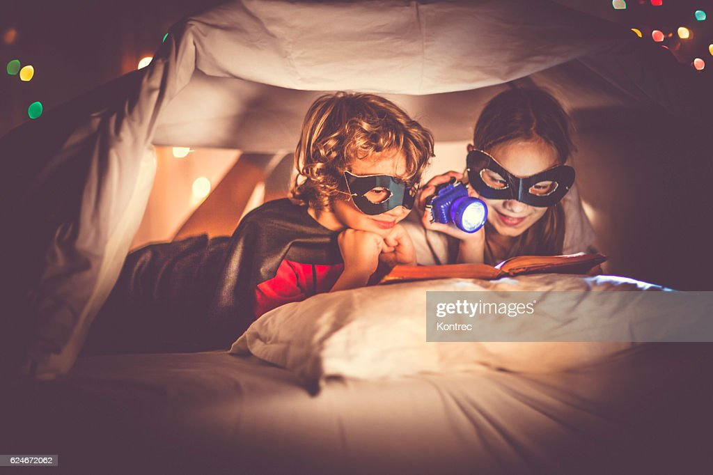 Children reading a book past their bedtime : Stock Photo