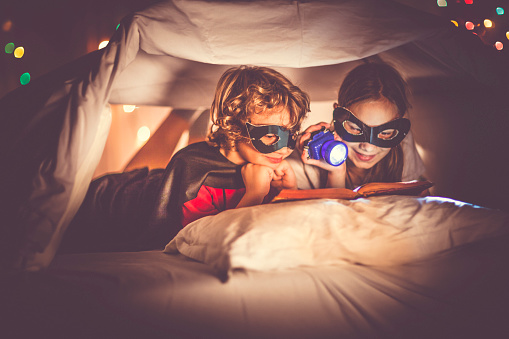 Children reading a book past their bedtime - gettyimageskorea