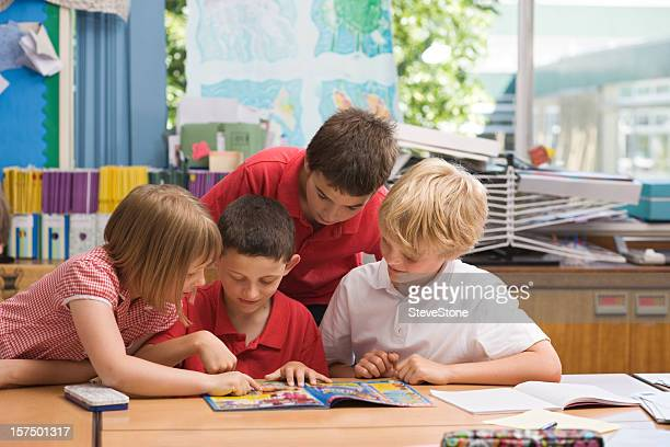 children reading a comic in school - comic book stock pictures, royalty-free photos & images