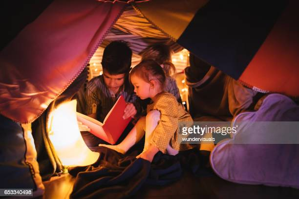 Children reading a story in blanket fort at night