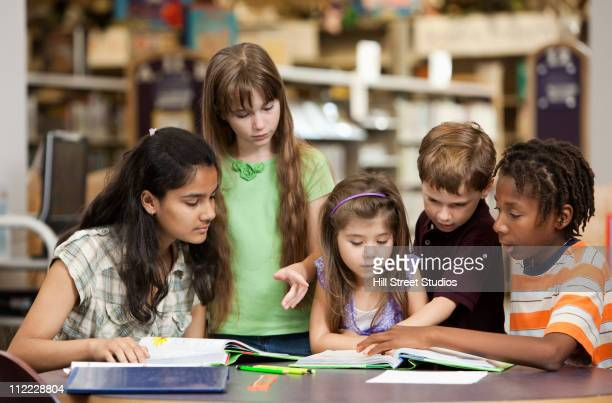 Children reading book together in library