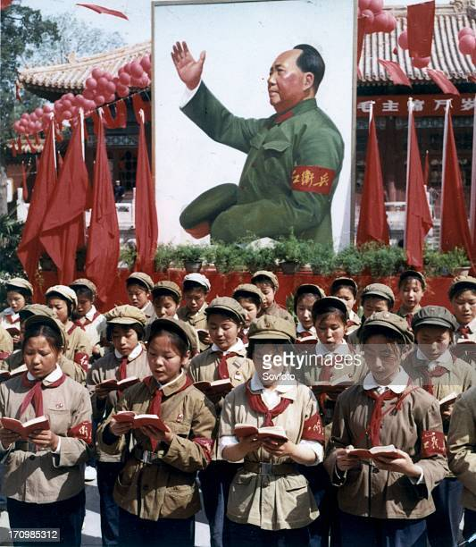 Children reading from mao's little red book at a rally with a portrait of mao in the background