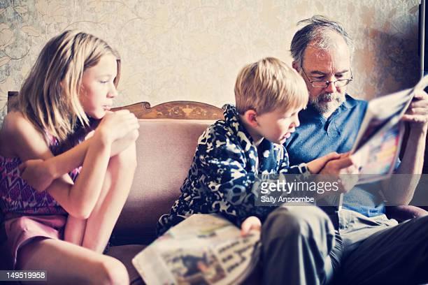Children reading newspaper with grandpa