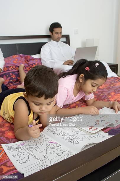 Children reading on the bed while father works