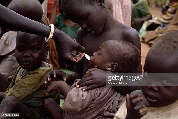 Children receive a meal at a feeding center in the refugee camp of Ame Sudan Civil war and widespread famine have ravaged Sudan for decades resulting...