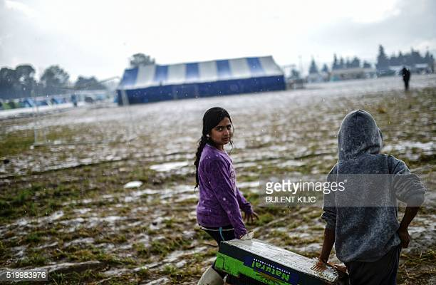 Children refugees carry food under the rain at their makeshift camp in the northern border village of Idomeni Greece on April 9 2016 Four migrant...