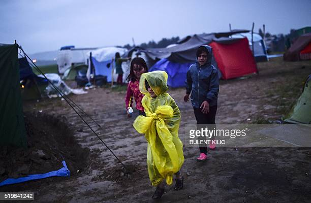 TOPSHOT Children refugees walk during rainy weather at a makeshift camp in the northern border village of Idomeni on April 8 2016 A plan to send back...