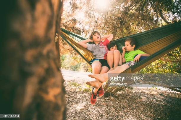 Children relax while camping in a hammock