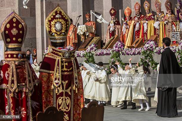 Children release birds as Armenian Apostolic Church leaders conduct a canonization ceremony for victims of the Armenian genocide at the Mother See of...