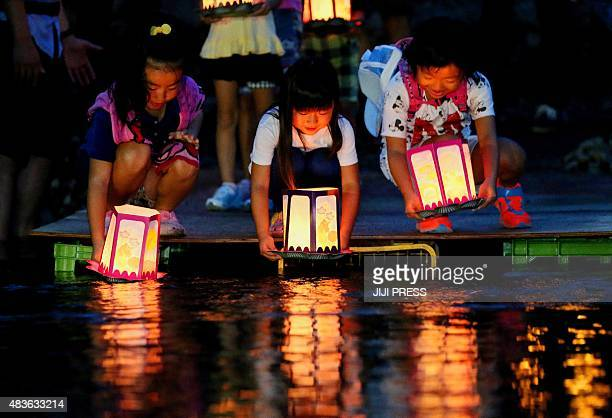 Children release lanterns in the river to offer prayers for the victims of Japan Airlines jumbo jet crash at Ueno village in Gunma prefecture north...