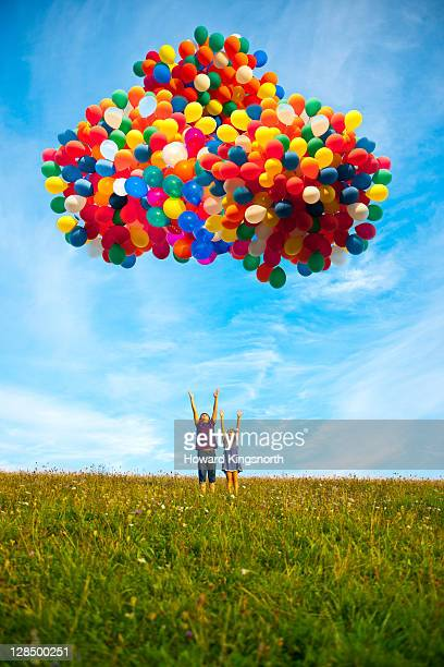 2 children releasing balloons