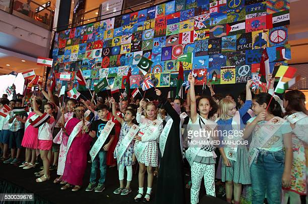 Children residing in Oman and representing 80 countries wave their national flags in front of a banner made out of their drawings during the opening...