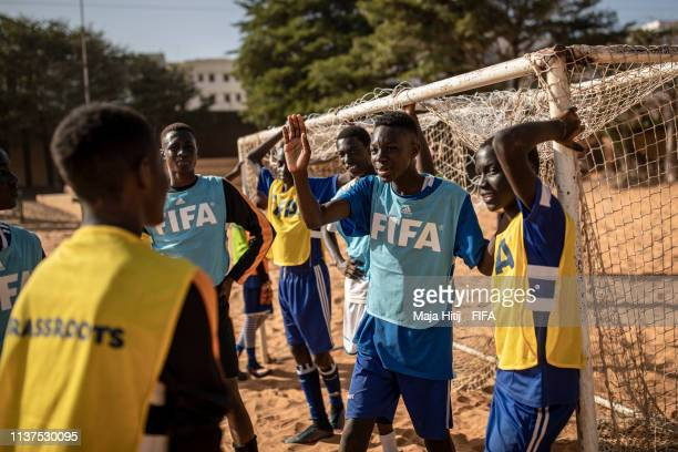 Children rest after playing football during a FIFA Grassroots schools program on January 16 2019 in Dakar Senegal